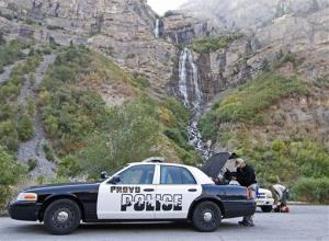 A Provo policeman pulls his gear out of his truck in Provo Canyon, east of Provo, Utah, Friday, Sept. 7, 2007.