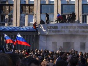 Pro-Russian activists with Russian national flags storm the Ukrainian regional office of the Security Service in Luhansk, Ukraine yesterday.