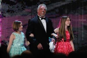 In this April 5, 2014 file photo, James Hellwig, aka Ultimate Warrior, is escorted by his daughters to the stage during the WWE Hall of Fame Induction.