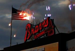 Fireworks burn an American flag at Turner Field at a baseball game between the New York Mets and Atlanta Braves, Tuesday, April 8, 2014.