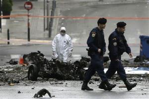 A police bomb disposal expert searches for evidence behind the remains of a car in central Athens.