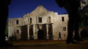 In this March 6, 2013, file photo, Dan Phillips, a member of the San Antonio Living History Association, patrols the Alamo during a pre-dawn memorial ceremony in San Antonio.