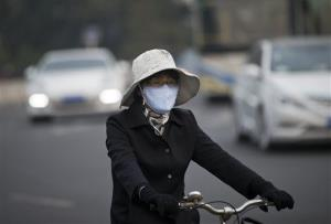 A woman wearing a face mask bicycles on a road in Beijing.