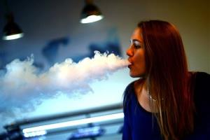 This Nov. 26, 2013 photo shows Steffani Leifeld exhaling a vapor at the Smokeless Smoking electronic cigarette store in Woodbury, Minn.