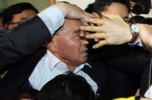 South Korean Prime Minister Chung Hong-won is shielded by his bodyguards from angry relatives of passengers.