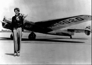 Amelia Earhart stands next to a Lockheed Electra 10E.