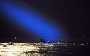Blue search light cast by South Korean Coast Guard helicopter shows a sunken ferry in the water off the southern coast near Jindo, South Korea, Thursday, April 17, 2014.
