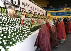 Buddhist monks pray for victims who were killed in the roof collapse of a resort building,  at a group memorial altar at a gymnasium in Gyeogju, South Korea, Tuesday, Feb. 18, 2014.