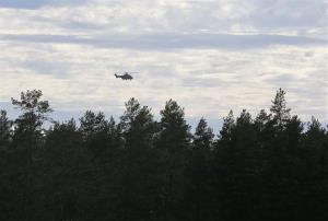 A helicopter flies over the area near the Jamijarvi Airfield, southwest Finland, where a small passenger plane carrying skydivers fell to the ground yesterday.