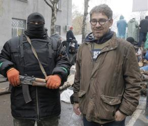 Reporter Simon Ostrovsky, right, stands next to a pro-Russia gunman at a seized police station in the eastern Ukraine town of Slovyansk last week.