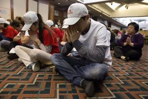 Relatives of Chinese passengers on board the Malaysia Airlines Flight 370 pray at a hotel conference room in Beijing, China, Friday, April 18, 2014.
