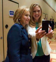 This 2013 photo released by Barbara Kinney shows Hillary Rodham Clinton posing with Chelsea at a Clinton Global Initiative America event in Chicago.