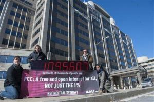 Members of global advocacy group Avaaz stand next to a digital counter showing the number of petition signatures calling for net neutrality outside the Federal Communication Commission in Washington.