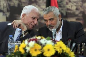 Senior Fatah official Azzam al-Ahmad, left, talks to Gaza's Hamas Prime Minister Ismail Haniyeh during a press conference after the announcement of an agreement between the two Palestinian groups.