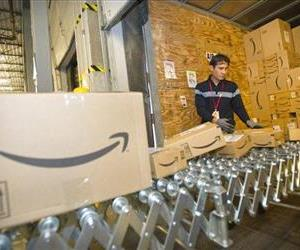 In this file photo, an Amazon.com team member loads boxes of fulfilled orders into a truck in a Fernley, Nev., warehouse.