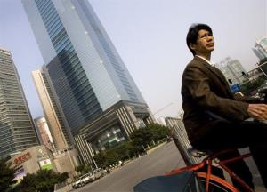 A Chinese man cycles past the financial district in Guangzhou, China, Tuesday, Nov. 27, 2007.