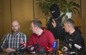 Vacheslav Ponomarev, self-proclaimed mayor of Slovyansk, right, speaks as two military observers, one Axel Schneider of Germany, left, look to each other in Slovyansk, Ukraine, April 27, 2014.
