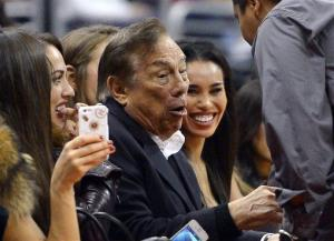 In this photo taken on Friday, Oct. 25, 2013, Los Angeles Clippers owner Donald Sterling, center, and V. Stiviano, right, watch the Clippers play the Sacramento Kings in Los Angeles.
