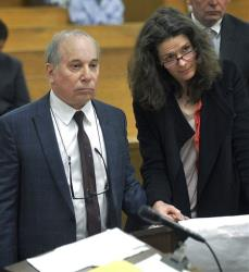 Singer Paul Simon, left, holds hands with his wife Edie Brickell at a hearing in Norwalk Superior Court on Monday April 28, 2014 in Norwalk, Conn.