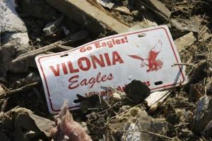 A Vilonia High School license plate sits in storm debris in Vilonia, Ark.