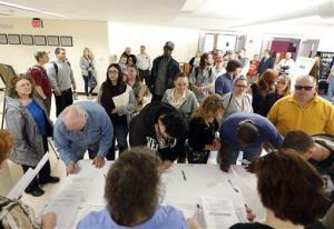 In this April 22, 2014 photo, job seekers line up for a job fair at Columbia-Greene Community College in Hudson, NY.