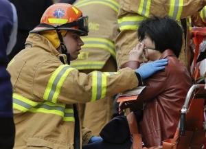 A New York City firefighter assists a woman who was evacuated from the subway train.