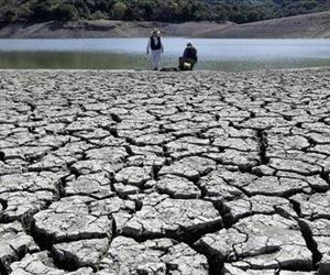 This Thursday, March 13, 2014 file photo shows cracks in the dry bed of the Stevens Creek Reservoir in Cupertino, Calif.