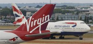 A British Airways 747 passes the tail fin of a Virgin Atlantic plane at Heathrow Airport, London, Friday, July 30, 2010.