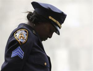 Sgt. Shannon Graham of the New York Police Department bows her head during the benediction during a ceremony at the State of New York Police Officers Memorial on Tuesday.