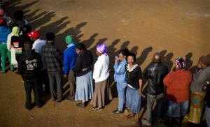 South Africans queue to vote at a polling station that was burned down overnight, but a tent was erected to vote at in the morning, in Bekkersdal, South Africa, Wednesday, May 7, 2014.