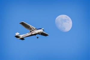 A Cessna 172 airplane flies over a nearly full moon in this Jan. 12, 2014 file photo.