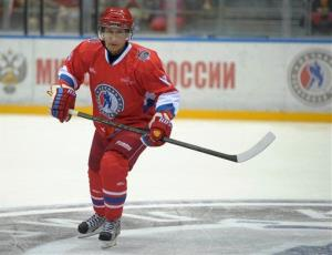 Vladimir Putin plays in a hockey match between Russian amateur players and stars at a festival of amateur hockey in the Olympic Park in Sochi, Saturday, May 10, 2014.
