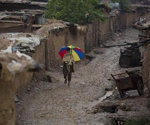 An Afghan refugee boy walks in an alley of a refugee camp in the rain in Islamabad, Pakistan, Monday, May 12, 2014.