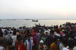 Bangladeshi people gather on the banks of the River Meghna after a ferry carrying more than 100 passengers capsized and sank after being hit by a storm in Munshiganj district, Bangladesh, May 15, 2014.