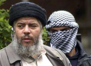 This Friday, April 30, 2004 file photo shows Muslim cleric Abu Hamza al-Masri, as he arrives with a masked bodyguard, right, to conduct Friday prayers in the street in London.