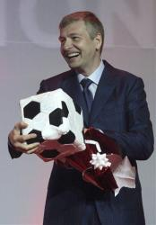 Dmitry Rybolovlev reacts after receiving a gift from Prince Albert II of Monaco. It's not clear whether he'll get to keep it.