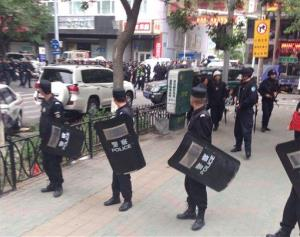 Police officers stand guard near a blast site which has been cordoned off in downtown Urumqi today.
