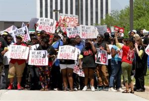 Protesters walk down Jorie Blvd. in Oak Brook, Wednesday, May 21, 2014 near the McDonald's Corp. headquarters in Oak Brook, Ill.