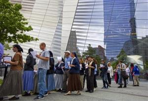 The reflective windows of the 9/11 Memorial Museum rise above some of the first public visitors to arrive at the site in New York Wednesday, May 21, 2014.