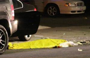 In this image provided by KEYT-TV, a body is covered on the ground after a mass shooting near the campus of the UC Santa Barbara in Isla Vista, Calif.