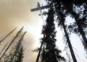 A plane sprays over a portion of a wildfire in the Funny River community of Soldotna, Alaska.