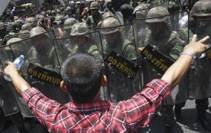An anti-coup demonstrator gestures in front of Thai soldiers during a protest in Bangkok, Thailand yesterday.