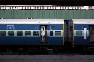 A man stands at the doorway of a train at a railway station in New Delhi, India, Wednesday, May 14, 2014.