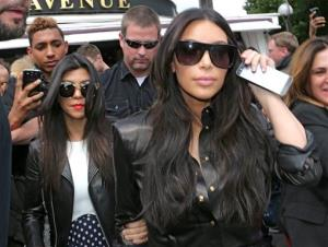 Kim Kardashian, front and Kourtney Kardashian, left, leave at a restaurant in Paris, Thursday, May 22, 2014.