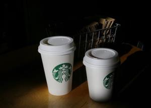 Tiny, non-$54 cups of Starbucks coffee sit on a counter at a Starbucks store.