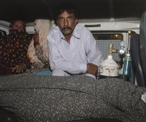 Muhammad Iqbal, right, husband of Farzana Parveen, 25, sits in an ambulance next to the body of his pregnant wife who was stoned to death by her own family, in Lahore, Pakistan.