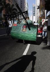 A shadow of a protester is seen in front of a mock tank, symbolizing the man blocking tanks at the 1989 movement, on a downtown street in Hong Kong, Sunday, June 1, 2014.