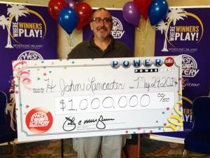 """In a Thursday, May 29, 2014 photo, Hartzell """"John"""" Lancaster of Weirton, W.Va., claims a $1 million Powerball prize from the West Virginia Lottery in Wheeling, W.Va."""