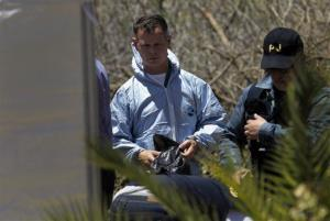 A British policeman, left, wearing a forensic suit and a Portuguese policeman stand by a tent inside a cordoned-off area, in Praia da Luz, Wednesday, June 4, 2014.
