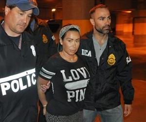 In this Monday, June 9, 2014 photo provided by the Drug Enforcement Administration, Samantha Barbash, center, is escorted by law enforcement officers following her arrest in New York.